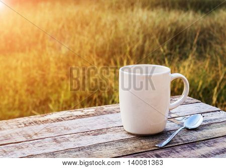 Coffee cup on wooden table with morning sunlight