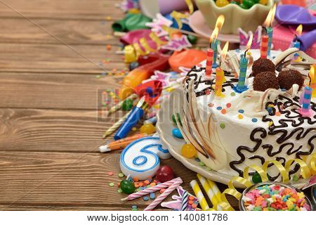 Birthday cake and various accessories for the holiday on a brown background