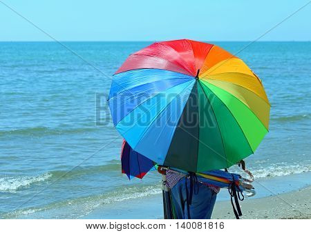 Peddler Of Umbrellas On The Beach In Summer