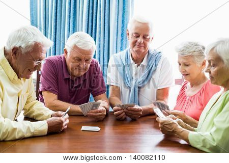 Senior playing cards together in a retirement home