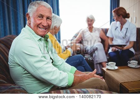 Portrait of a smiling retired man looking at the camera seated on a sofa