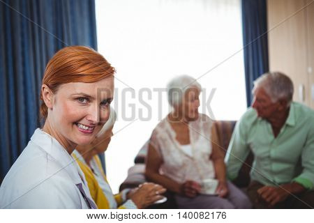 Portrait of a smiling nurse with seniors in a retirement home