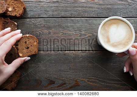 Eating rye bread with coffee, copyspace, wooden background. Top view on female hands holding bread slice and cup of cappuccino, eater pov