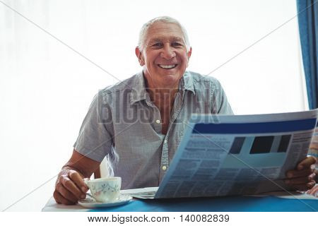 Retired smiling man looking at the camera while holding newspaper