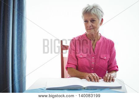 Portrait of a worried retired woman with hand on the table
