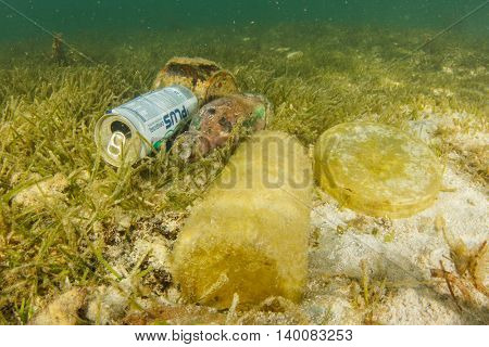 MABUL, MALAYSIA - CIRCA JULY 2016: Plastic pollution in ocean. Bottles, cans and bags dumped in sea.