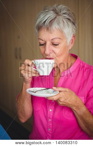 Portrait of a smiling woman drinking a tea