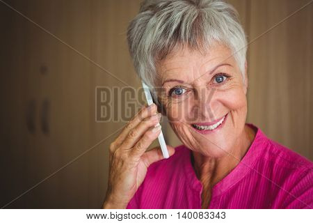 Portrait of a smiling retired woman making a call