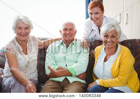 Portrait of smiling retired person looking at the camera seated on a sofa