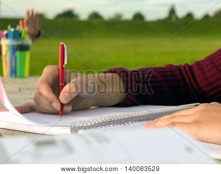 outdoors at a wooden table female hand writing in a notebook, burgundy sweater, green grass , for the background box of crayons and a child hands
