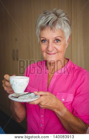 Portrait of a smiling retired woman holding a cup of tea