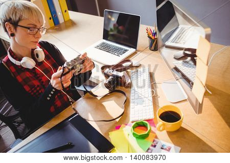 Female graphic designer looking at pictures in digital camera at office