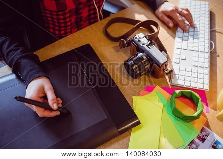Mid section of female graphic designer using graphic at office
