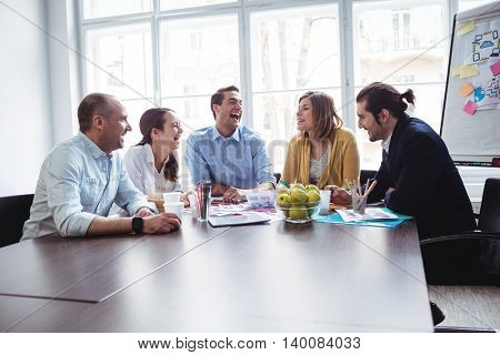 Happy colleagues discussing in meeting room at creative office