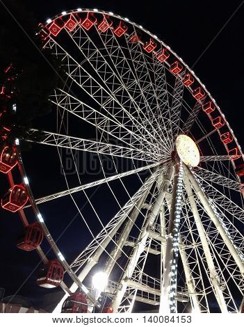 Part of ferris wheel against a black sky background with lights neby night lighting