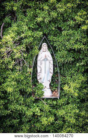 Mary statue and greenery. Religious object. Symbol of christianity. Vertical composition.