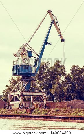 Blue crane in cargo port translating coal. Industrial scene. Retro photo filter. Vertical composition.