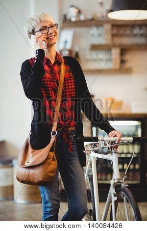 Happy young woman standing along with bicycle talking on mobile phone