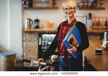 Portrait of happy young woman standing along with bicycle at office cafeteria