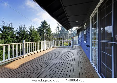View Of Wooden Walkout Deck With White Railings.