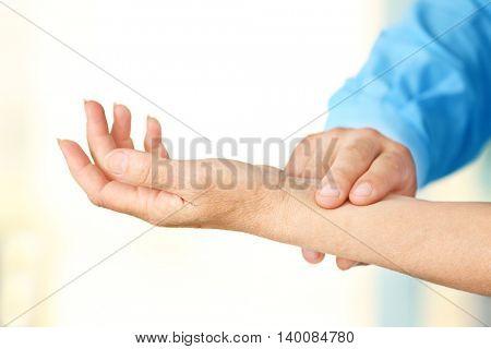 Male doctor measuring woman pulse