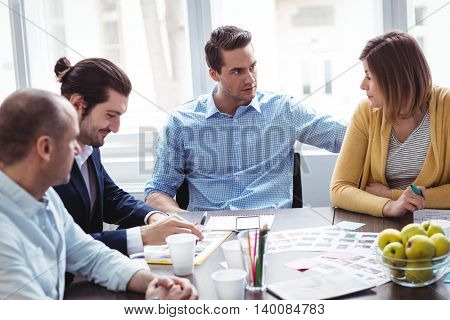 Photo editors discussing in meeting room at creative office