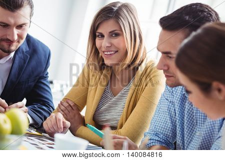 Portrait of smiling female photo editor with colleagues working in creative office