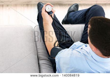 Man measuring blood pressure himself with tonometer