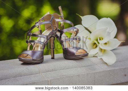 Bride's shoes and bouquet of callas in the park