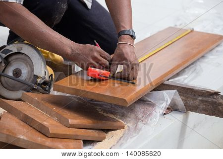 Carpenter Use Measure Tape To Measuring Wood