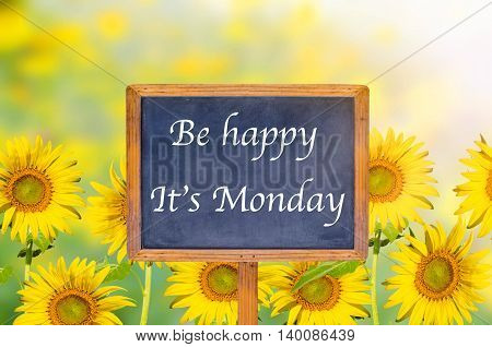Be happy it's monday on signpost in beautiful sunflower background