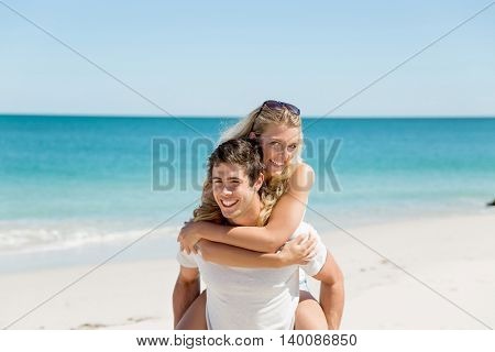 Portrait of man carrying girlfriend on his back