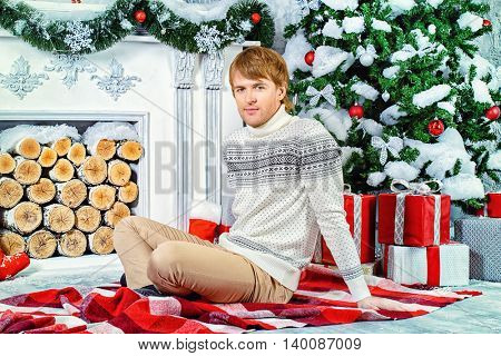 Joyful young man celebrating winter holidays by the fireplace beautifully decorated for Christmas.