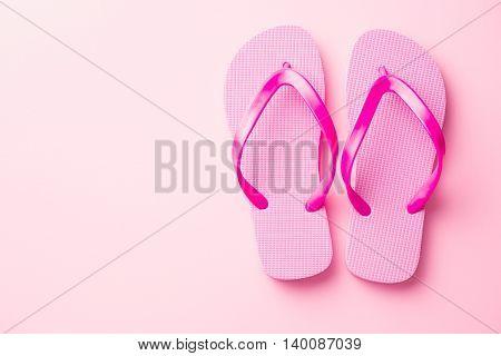 Pink flip flops on pink background.