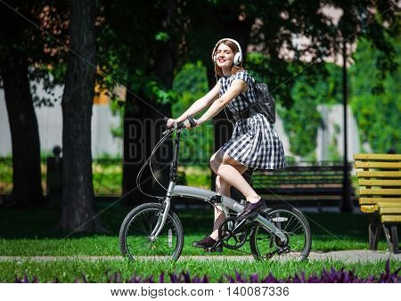 Teen student girl or young woman in plaid dress rides a folding bicycle and listens music in white earphones in the park. Summer healthy leisure in town