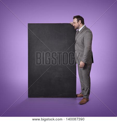 Blank blackboard with businessman standing side office