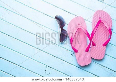 Pink flip flops and sunglasses on blue floor.
