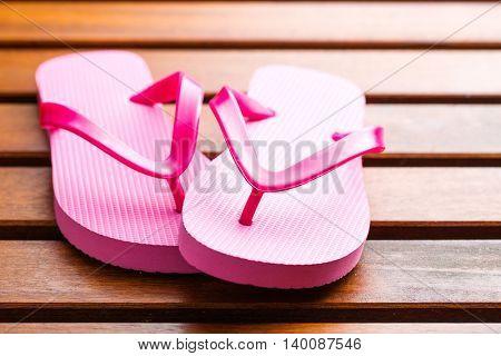 Pink flip flops on wooden floor.