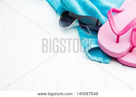 Pink flip flops with towel and sunglasses on white floor.