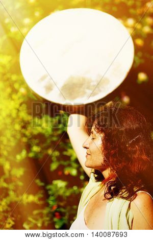 girl holding a shamanic frame drum in her hand in the nature. solar light effect