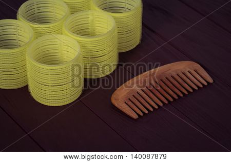 Still life yellow hair rollers with wooden comb on a dark background closeup