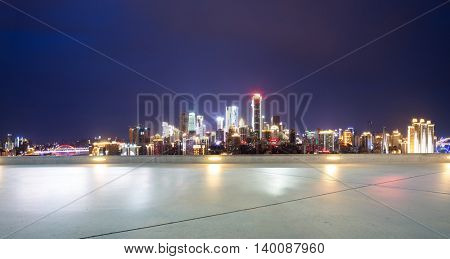 cityscape and skyline of chongqing at night on view from empty floor
