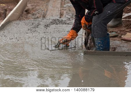 Hand Of Worker Use Trowel Plastering A Newly Poured Concrete Floor
