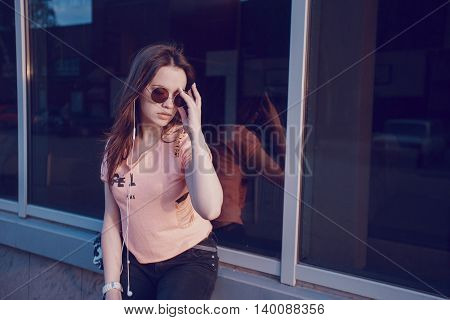 stylish girl walking in the evening city with a phone and a headset