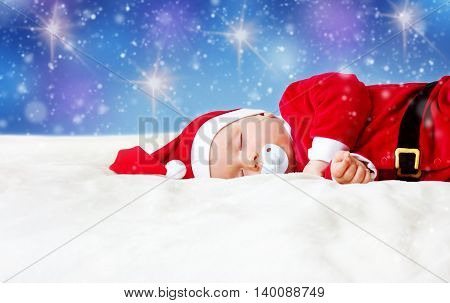 little baby sleeping in red hat on white blanket. Eight month old child in santa costume