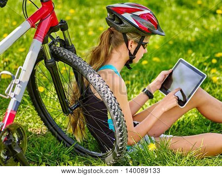 Bicycle girl. Girl rides bicycle. Girl in bicycling sitting near bicycle and watch pc tablet. Bicycle is good for health. Cyclist looking for pc tablet