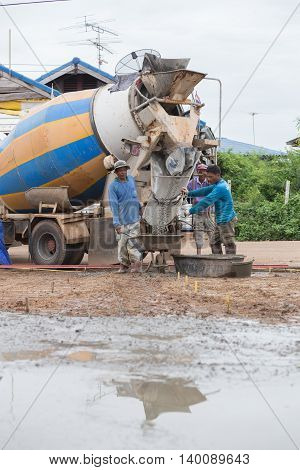 A Cement Truck Is Pouring Cement To Cart At Consrtuction Site