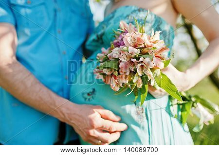 Happy pregnant couple. Close up belly with bouquet