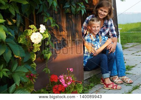 Parent and child sitting on the steps of the house in the garden