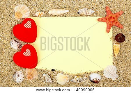blank paper with love hearts and seashells on sand love background